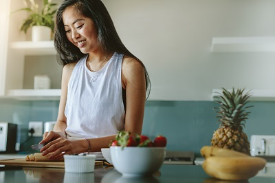 Woman preparing healthy salad from fresh fruits in the kitchen.