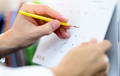 Cropped view of man hand holding yellow pencil circling the date on calendar.