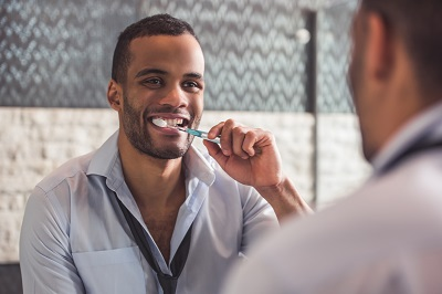 Handsome Afro American businessman is brushing his teeth while looking into the mirror in bathroom
