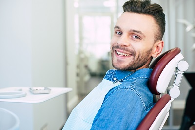 Happy man with hazel eyes and dark brown hair is sitting in dental chair and smiling right into the camera