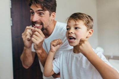 Little boy with his father in bathroom cleaning teeth with dental floss.