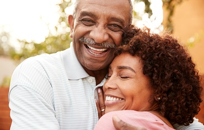 Senior african american man and his middle aged daughter embracing