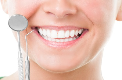 Closeup of perfect smile and dentist tools on white background
