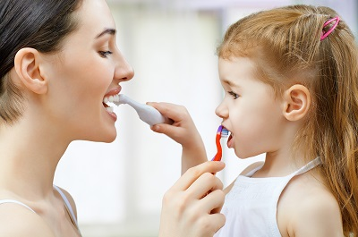 mother teaching daughter how to brush teeth