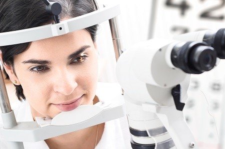 female patient getting her eye examined at optometrist