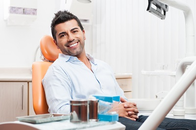 handsome man smiling while waiting at the dental chair
