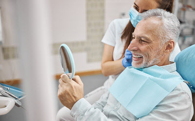 senior patient looking at his smile with mirror in dental office