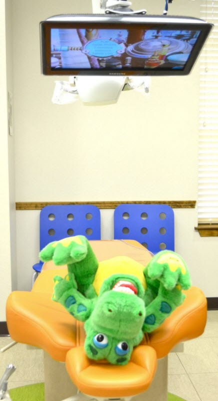 A look at one of our examination chairs with a stuffed gator watching the TV above it at Alligator Dental, a pediatric dentist located in Sequin, Texas.  Accepting new patients now!