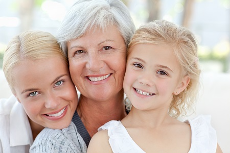 mature woman being embraced by her grandchildren