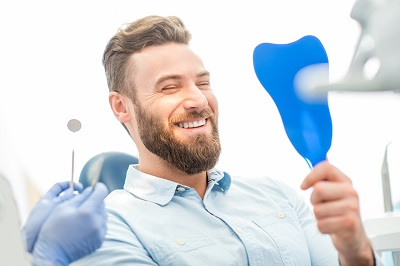 Handsome male patient looking at his beautiful smile sitting at the dental office