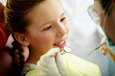 Close up portrait of a little smiling girl at dental office getting a checkup