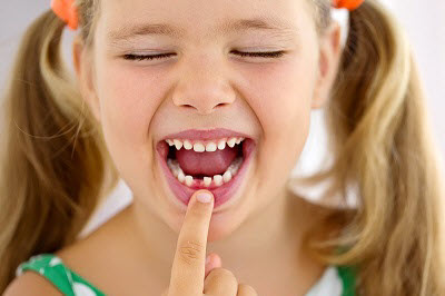 little girl pointing at missing primary teeth