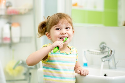 kid girl brushing teeth in bath room
