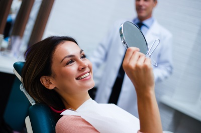Beautiful young woman looking at her smile on a mirror in the dentist's office