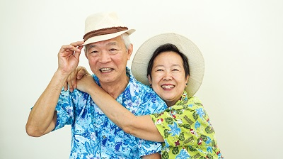 Asian senior couple happy for holiday plan ahead wearing Hawaii shirt and hat