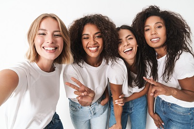group of friends taking selfie with white background