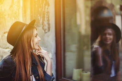 Portrait of young smiling woman looking at shop window