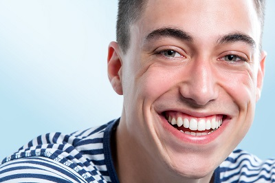 close up face shot of Young man with charming and healthy toothy smile