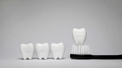 Tooth model in happy emotion and black toothbrush