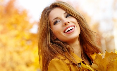 woman smiling in park during autumn