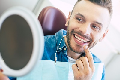 male patient checking out his smile with mirror at dental chair