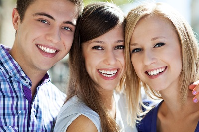 three young people with whitened teeth smiling