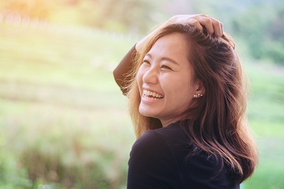 Asian woman smiling with perfect smile in the green nature