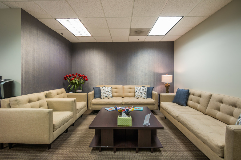 the waiting room, couches, and table within the front office